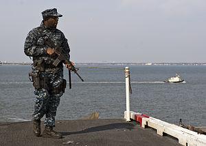 US Navy 120210-N-FI736-038 Aviation Ordnanceman Airman Breon Jones stands watch as the aircraft carrier USS Enterprise (CVN 65) pulls into port.jpg