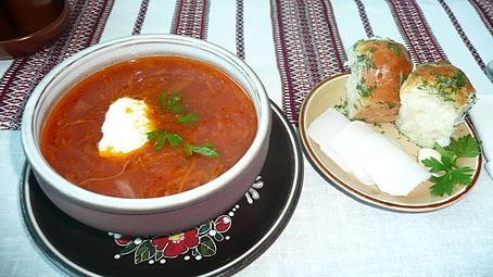 A bowl of red borscht served with two garlic pampushky and three slices of salo on a separate plate