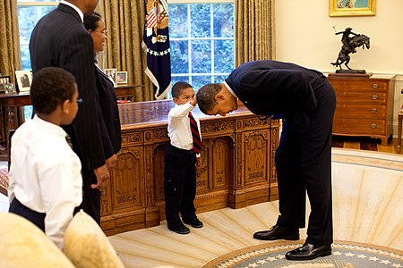United States President Barack Obama bends down to allow the son of a White House staff member to touch his head