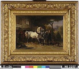 Interieur van een stal met paarden en een stalknecht
