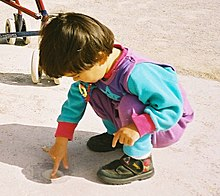 Young Child Playing At Ease In A Squatting Position Children