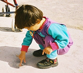 Squatting position - Young girl playing at ease in a squatting position