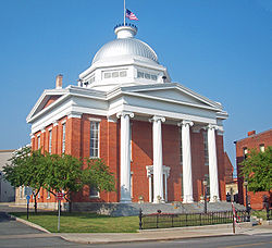 A brick building with four white columns in front and a silvery dome on top