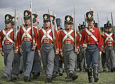 Photo of men dressed in British uniforms of the early 1800s. They wear red coats with white cross belts, gray trousers, and black shakos.