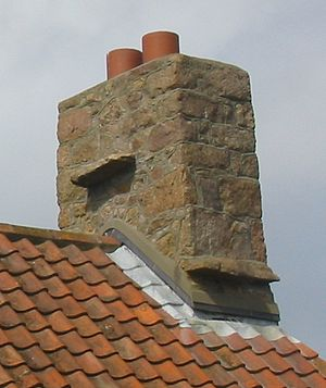 Flashing (weatherproofing) - Weatherproofing seam between a stone chimney and a tile roof on a building in Jersey, Channel Islands. The lead flashing is seen as light gray sheets at the base of the chimeny.