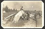 """Crash at Mohawk"" Group of men working on a crashed aircraft next to the railway line at Camp Mohawk, one of the Royal Flying Corps' pilot training camps near Deseronto, Ontario. (7980863710).jpg"