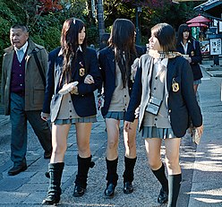 0b6ee9bbb Kogal girls, identified by shortened Japanese school uniform skirts. In the  left image, they are also wearing loose socks.