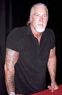 White male with gray hair and arm tattoos wearing a black shirt