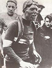 Photographie en noir et blanc d'un cycliste couvert de boue à l'arrivée d'une course.