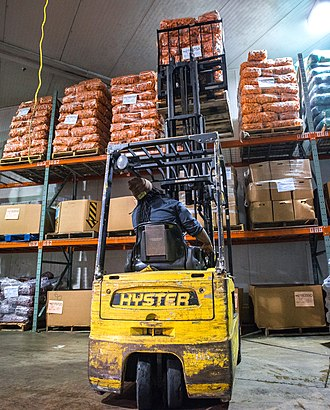 Food distribution - A man using a forklift to unload carrots from a refrigerated truck at a warehouse in Long Island City, New York