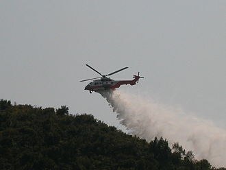 Government Flying Service - Hong Kong Government Flying Service Eurocopter AS-332L2 putting out a hill fire with a belly mounted water tank