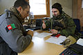 A Norwegian soldier, right, discusses training operations with a Ukrainian soldier playing the role of an Afghan National Police officer during a military adviser team (MAT) and police adviser team (PAT) 131210-A-RJ750-012.jpg