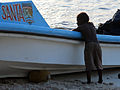 A small boy leans against a boat with 'Santa Ana' written on it. (10663482493).jpg