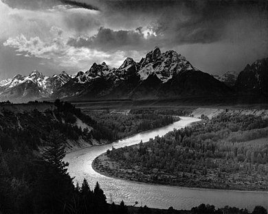 A dramatically lit black and white photograph depicts a large river which