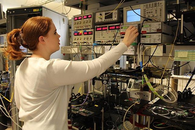 Physikerin beim Einrichten eines Experiments image source