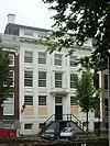 foto van Dubbel huis met zandstenen van festoenen voorziene gevel onder rechte lijst en attiek, evenals de gebeeldhouwde ingangspartij met balcon