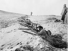 Black and white photo of a group of men wearing military uniforms crouched in a trench in rocky terrain. The men are all aiming rifles forward. Several men are standing behind the men in the trench.