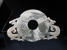 Photographie montrant un objet en jade blanc composé d'une partie centrale en forme de disque à décor de petites spirales percé d'un trou en son centre et ornée de part et d'autre de sculptures de dragons.