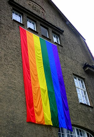 Big rainbow flag hanging on side of building
