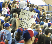 "A fan holds a sign that reads ""BRING BACK EXPOS""."