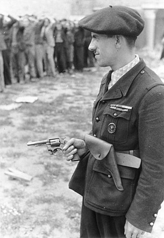 Milice - Milice member guarding Resistance PoWs wearing a German Army Wound Badge (indicating previous service with a German Army unit) and armed with a Spanish copy of the Smith & Wesson Model 10 revolver, chambered in 8mm French Ordnance.