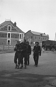 Two wounded Commandos escorted by two armed German naval personnel. A large building is in the background