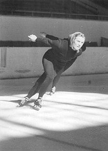 Helga Haase, portant un fichu sur la tête, pendant une course en intérieur. On voit le bras et le patin d'une concurrente derrière elle.