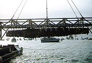 H. L. Hunley, suspended from a crane during its recovery from Charleston Harbor, August 8, 2000. (Photograph from the U.S. Naval Historical Center.)