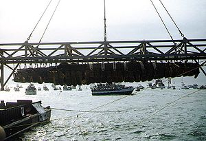 E. Lee Spence - H. L. Hunley, suspended from a crane during its recovery from Charleston Harbor, August 8, 2000. (Photograph from the U.S. Naval Historical Center.)