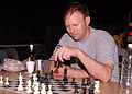 Capt. Tyler Carruth, medical provider with the Texas Medical Command, plays chess at Contingency Operating Base Basra. During his deployment to Iraq, Carruth was responsible for testing a blue-tooth 110808-A-JX739-007.jpg