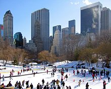 An outdoor skating rink with many people on the rink. There are skyscrapers in the background. This is the Wollman Rink in Central Park