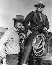 la photo noir et blanc montre à gauche Clint à pied, à côté d'un cavaler monté. Ils portent le costume des cow-boys et un lasso pend à la selle.