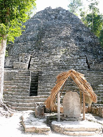 "Coba - Front view of the pyramid structure known as ""La Iglesia"" in the Group B, or Cobá Group, complex. Stela 11 is in the foreground at the base of the pyramid's steps, under the thatched roofing."