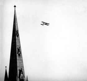 Cathedral spire with biplane in level flight in the distance