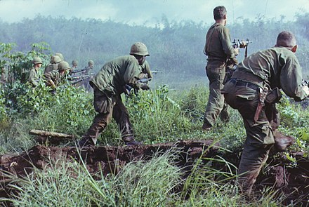 A U.S. Army infantry patrol moves up to assault the last North Vietnamese Army position at Dak To, South Vietnam during Operation Hawthorne DakToVietnam1966.jpg