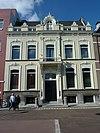 foto van Pand met verdieping en zadeldak. Inwendig kelder met graatgewelven. Trap met balusterleuning 18e eeuw; deuren uit de bouwtijd. Rijke gevel, derde kwart 19e eeuw in eclectische, aan de renaissance, het Lodewijk XVI en het Empire ontleende vormen