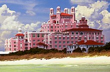 A pink, multi-floor hotel stands out above a calm sea and a windswept beach.
