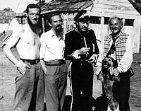 1948 B&W photograph of Donn Reynolds (far left) on the film set of Eureka Stockade standing with Peter Finch, Grant Taylor, and Sid Hermann (New South Wales, Australia).
