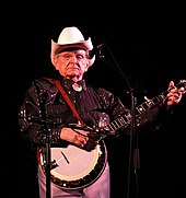 An older man wearing a white cowboy hat and a black dress shirt, standing behind a microphone stand and holding a banjo.