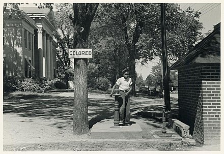 Segregated drinking fountain during the Jim Crow era, Halifax, 1938. Drinking fountain on the county courthouse lawn, Halifax, North Carolina.jpg