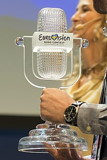 Photograph of a man (cropped out) holding the Eurovision trophy: a glass structure shaped to look like a retro microphone from the 1950s