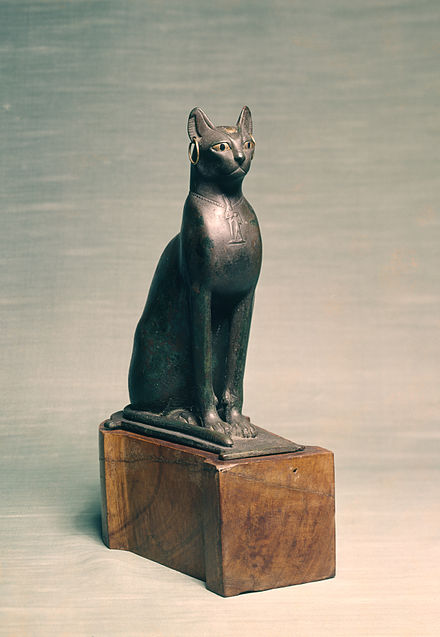 this seated cat has golden earrings a golden scarab inlaid on the forehead and