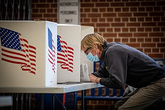 A masked voter casts a ballot at Roosevelt High School in Des Moines, Iowa Election Day 2020 (50564518207).jpg