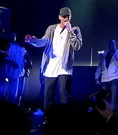 Eminem onstage in a white shirt, gray jacket and baseball cap