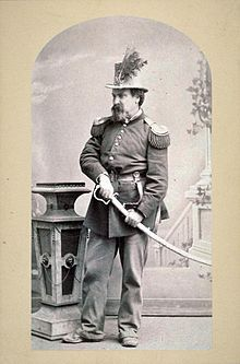 Joshua Norton in full military regalia with his hand on the hilt of a ceremonial sword.