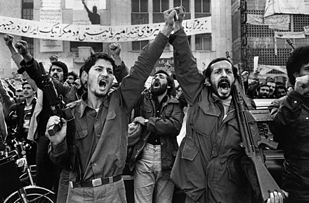 "Two armed men during demonstrations, behind of them is written: ""Long live anti-Imperialism and Democratic forces"". Enghlab Iran.jpg"
