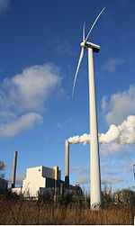 Picture showing smoke from chimneys and wind turbines indicating old and new human uses of the atmosphere