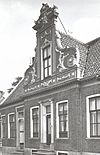 foto van Bakstenen huis, waarvan de brede voorgevel een middenrisaliet heeft, bekroond met een zeer rijk versierd voorschot met Lodewijk XV- en Lodewijk XVI-motieven