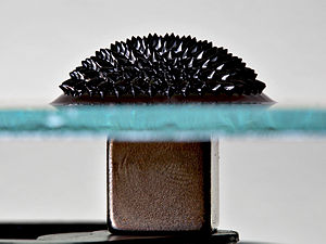 Ferrofluid - Ferrofluid on glass, with a magnet underneath.