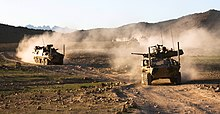 Colour photo of five military armoured fighting vehicles driving through dusty terrain